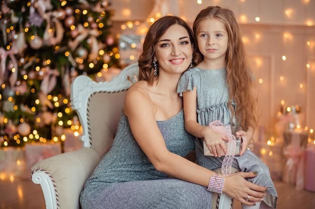 Szczęśliwego nowego roku! matka i córka dają sobie nawzajem prezent na tle świątecznych lei w domu