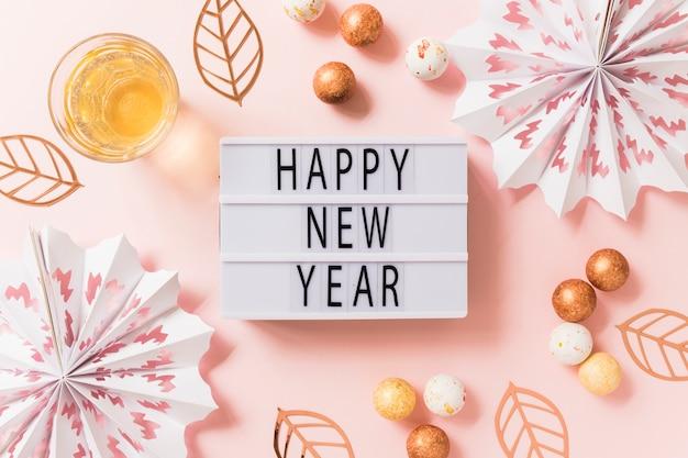 Szczęśliwego nowego roku napis na białej tablicy z kulkami