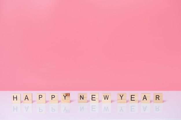 Szczęśliwego nowego roku z kostką drewna na różowym tle.