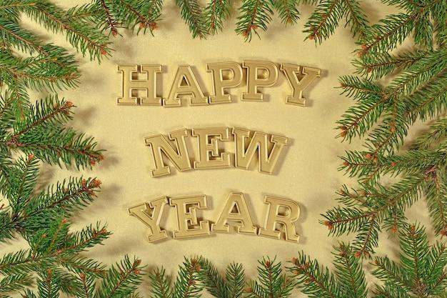 Szczęśliwego nowego roku złoty tekst i gałąź świerkowa na złotym tle