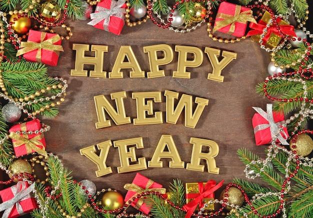 Szczęśliwego nowego roku złoty tekst i świerkowa gałąź i ozdoby świąteczne na drewnianym tle
