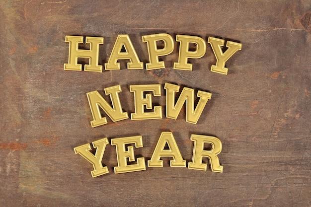 Szczęśliwego nowego roku złoty tekst na drewnianym tle