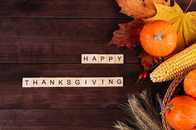 Szczęśliwego święta dziękczynienia. dojrzałe pomarańczowe dynie, pszenica i kukurydza na brązowym tle drewnianych.