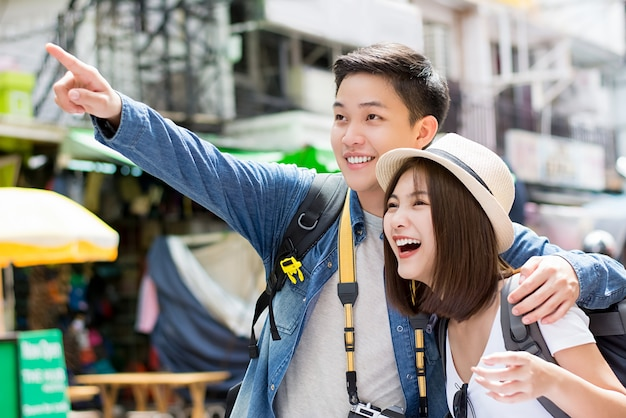 Szczęśliwej azjatyckiej pary turystyczni backpackers podróżuje w khao san drodze, bangkok