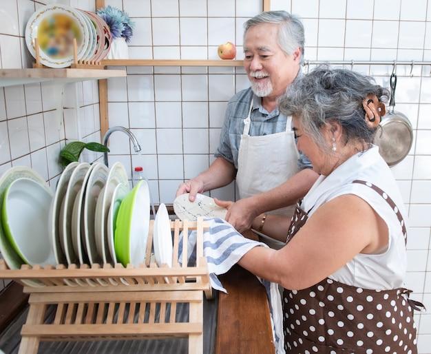 Szczęśliwej azjatykciej starszej osoby pary starszy domycia naczynia w zlew w domu w kuchni w domu.