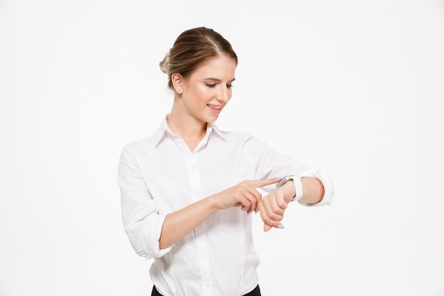 Szczęśliwej blondynki biznesowa kobieta używa jej wristwatch nad biel ścianą