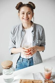 Szczęśliwej kobiety mienia uśmiechnięty szkło z grapefruitowym detox smoothie nad biel ścianą. zdrowa dieta.