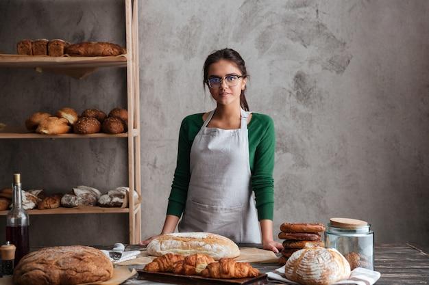 Szczęśliwej młodej damy piekarniana pozycja przy piekarnią blisko chleba.