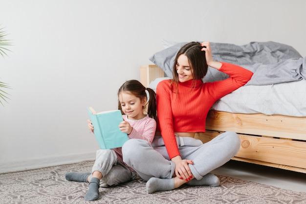 Szczęśliwej rodziny matki i dziecka córki mienia książkowy czytelniczy lying on the beach w łóżku