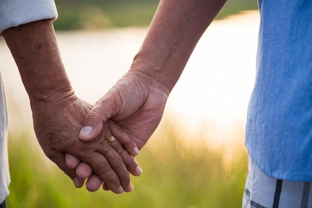Szczęśliwej starszej pary azjatykci stary mężczyzna i kobiety mienia ręka