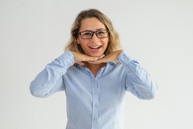 Szczęśliwej z podnieceniem damy oparta głowa na rękach i patrzeć kamerę