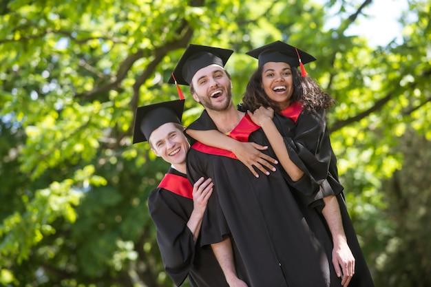 Szczęśliwi absolwenci. grupa absolwentów stojących w parku i czujących się niesamowicie