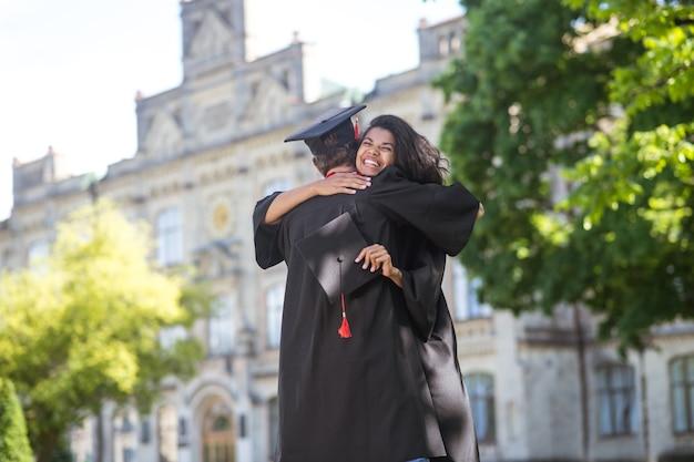 Szczęśliwi absolwenci. przyjaciele przytulają się po maturze i czują się szczęśliwi