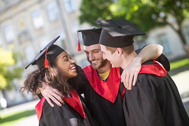 Szczęśliwi absolwenci. trzech absolwentów przytula się i rozmawia o ukończeniu studiów