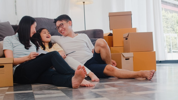 Szczęśliwi azjatyccy młodzi właściciele domów kupili nowy dom. chińska mama, tata i córka obejmując się niecierpliwie czekają na przyszłość w nowym domu po przeprowadzce w celu przeprowadzki, siedząc razem na podłodze z pudełkami.