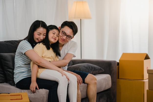 Szczęśliwi azjatyccy młodzi właściciele domów kupili nowy dom. japońska mama, tata i córka obejmując się niecierpliwie czekają na przyszłość w nowym domu po przeprowadzce i przeprowadzce, siedząc razem na kanapie z pudełkami.