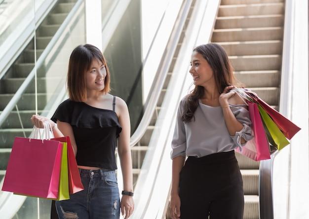 Szczęśliwi azjatykci dziewczyna przyjaciele z kolorowymi papierowymi torbami przy zakupy centrum handlowym