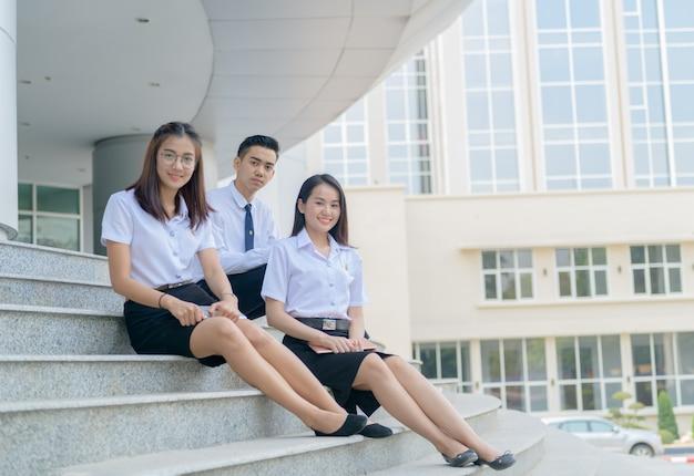 Szczęśliwi azjatykci ucznie w mundurze jest usytuowanym przy uniwersytetem