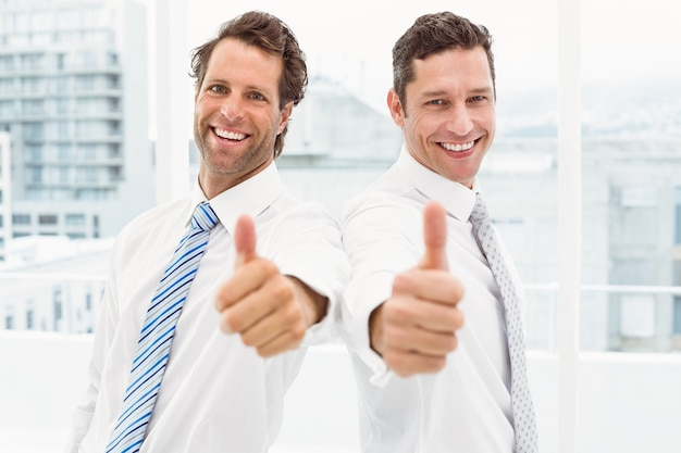 Szczęśliwi biznesmeni gestykuluje aprobaty w biurze