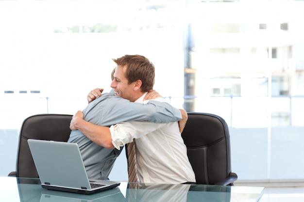 Szczęśliwi biznesmeni gratuluje each inny na sukcesie