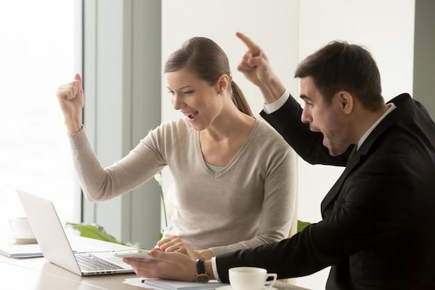 Szczęśliwi biznesmeni świętuje online biznesowego sukces