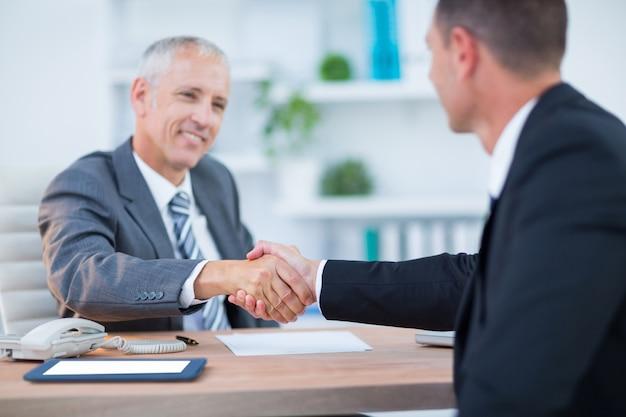 Szczęśliwi biznesmeni trząść ręki