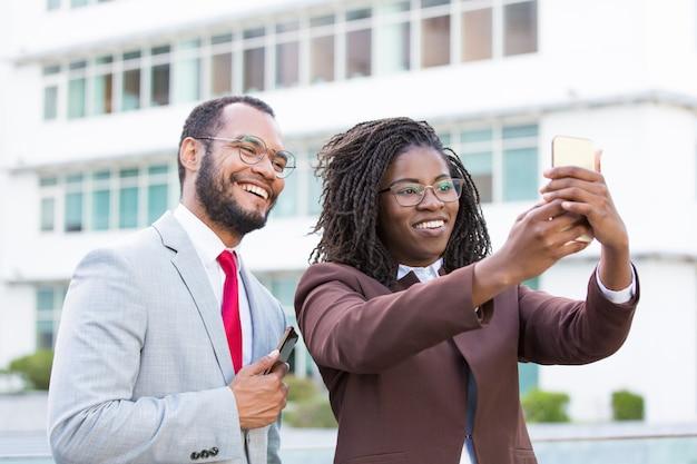 Szczęśliwi biznesowi koledzy bierze selfie outside