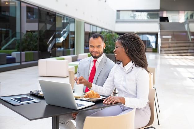 Szczęśliwi biznesowi koledzy ma śniadanie w kawiarni