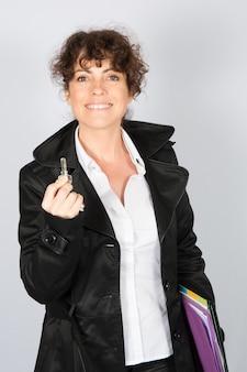 Szczęśliwi bizneswomanu mienia klucze dla klientów