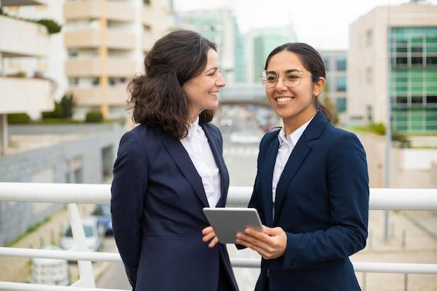 Szczęśliwi bizneswomany z cyfrową pastylką