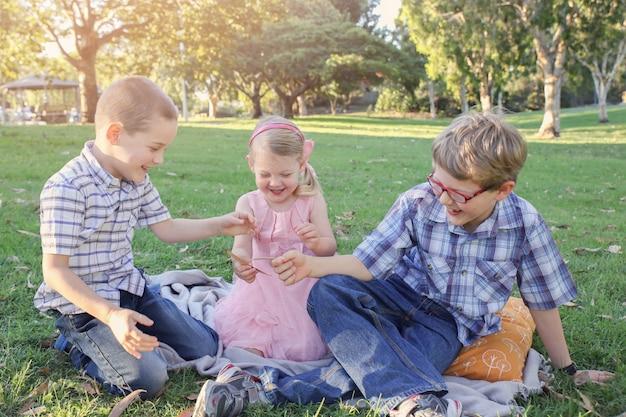 Szczęśliwi bracia i siostra bawić się w parku