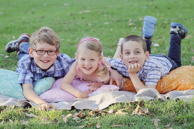Szczęśliwi bracia i siostrzany portret przy parkiem, tonuje