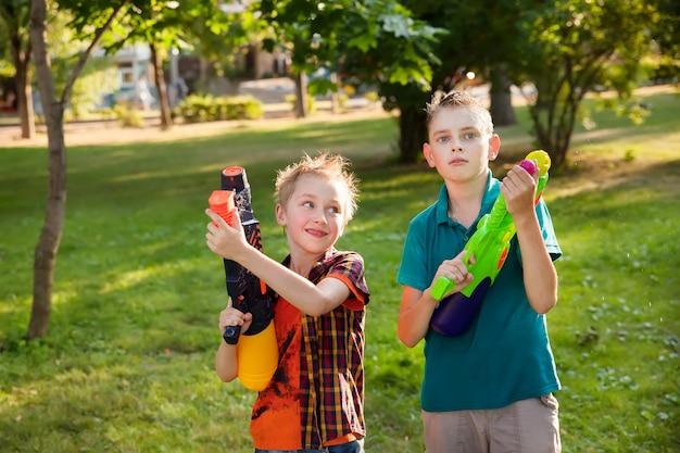 Szczęśliwi chłopcy bawią się pistoletami na wodę
