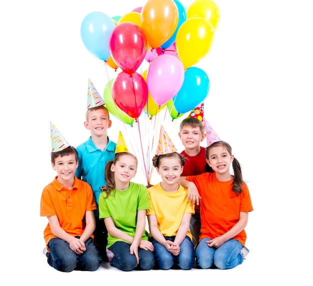 Szczęśliwi chłopcy i dziewczęta w czapce z kolorowych balonów, siedząc na podłodze - na białym tle