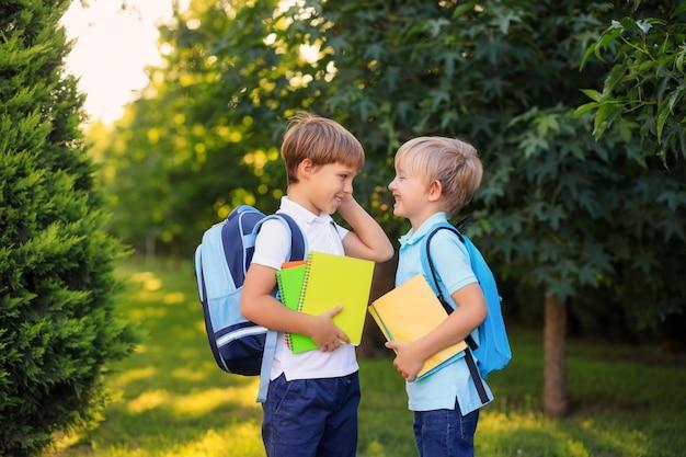 Szczęśliwi chłopcy z plecakami i książkami wracają do szkoły.