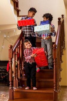 Szczęśliwi chłopcy ze świątecznymi prezentami dzieci trzymające prezenty na schodach trzej szczęśliwi bracia dzielą się w...