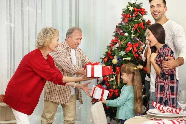 Szczęśliwi członkowie rodziny wręczają sobie prezenty świąteczne