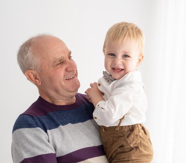 Szczęśliwi, dobrze wyglądający starsi mężczyźni z jego uroczym wnukiem w pomieszczeniu.