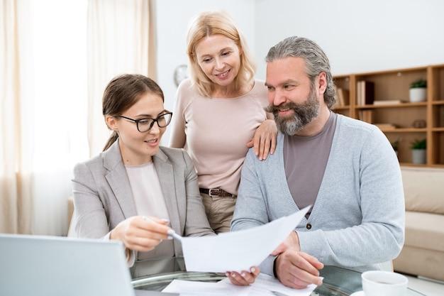 Szczęśliwi dojrzali małżonkowie słuchający agentów nieruchomości lub ubezpieczeniowych podczas omawiania głównych punktów dokumentu
