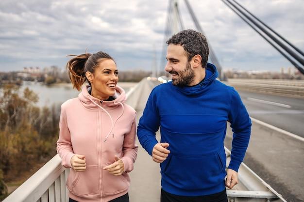 Szczęśliwi dopasowani sportowi heteroseksualni przyjaciele biegający po moście i rozmawiający. outdoor fitness na koncepcji pochmurnej pogody. miejskie życie.