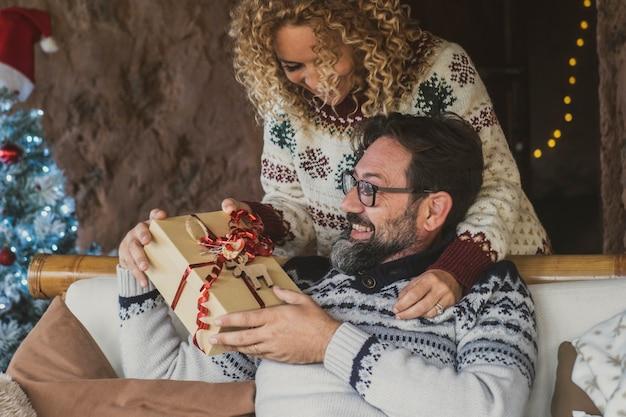 Szczęśliwi dorośli ludzie cieszą się świąteczną wymianą prezentów w domu