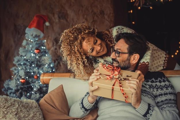Szczęśliwi dorośli ludzie w domu z prezentem świątecznym i dekoracjami