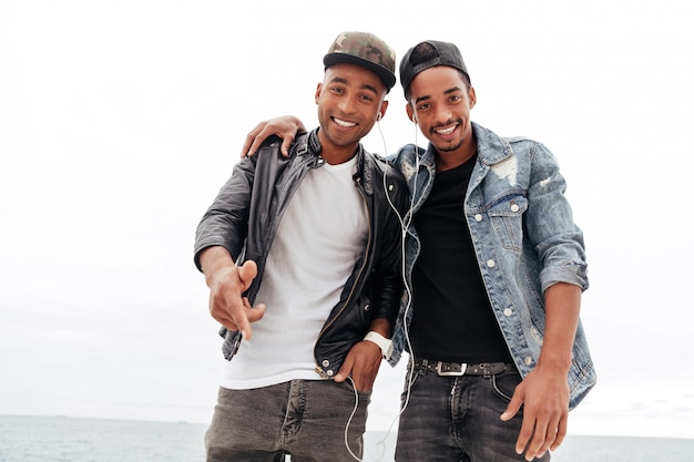 Szczęśliwi dwa młodego afrykańskiego mężczyzna przyjaciela słucha muzykę.