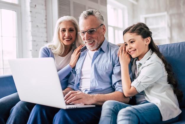 Szczęśliwi dziadkowie i dziewczyna siedząca z laptopem