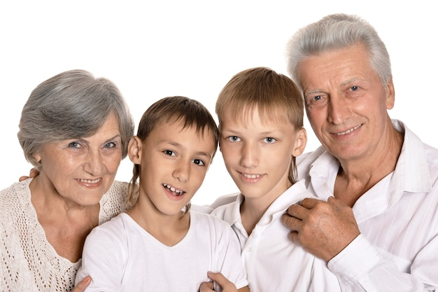 Szczęśliwi dziadkowie i ich dwoje wnuków na białym tle