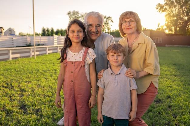 Szczęśliwi dziadkowie i wnuki stojące przed kamerą