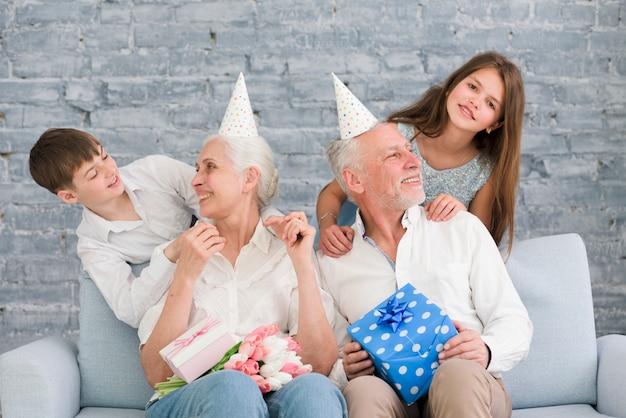 Szczęśliwi dziadkowie patrząc na swoje wnuki cieszące się przyjęciem urodzinowym