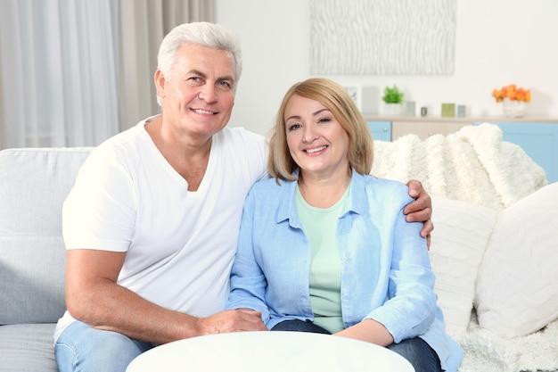 Szczęśliwi dziadkowie siedzą w domu w salonie