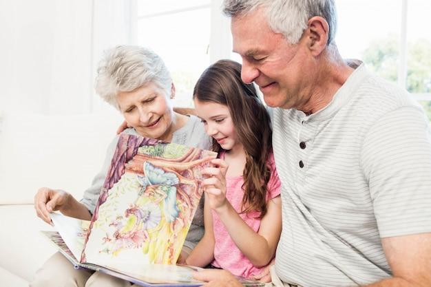 Szczęśliwi dziadkowie z wnuczką czyta książkę na kanapie