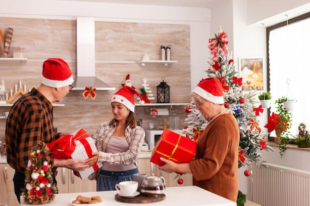 Szczęśliwi dziadkowie zaskakują świątecznym opakowaniem ze wstążką na nim